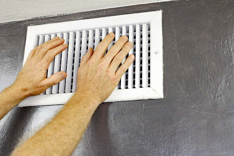 ac unit blowing hot air, a pair of adult male hands feeling the flow of air coming out of air vent
