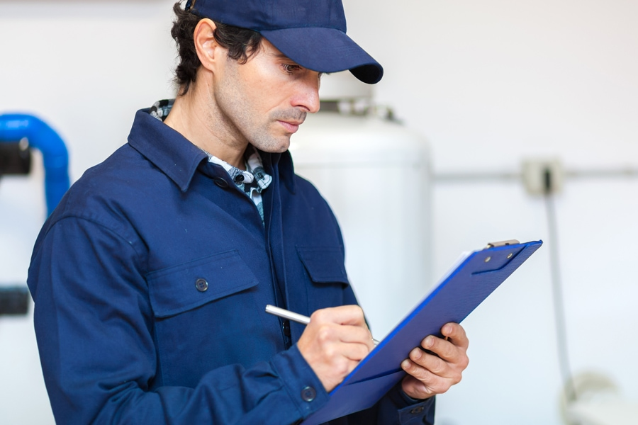 A repair man taking notes on a clipboard | Schedule Your Annual Furnace Inspection Now | Boise, ID