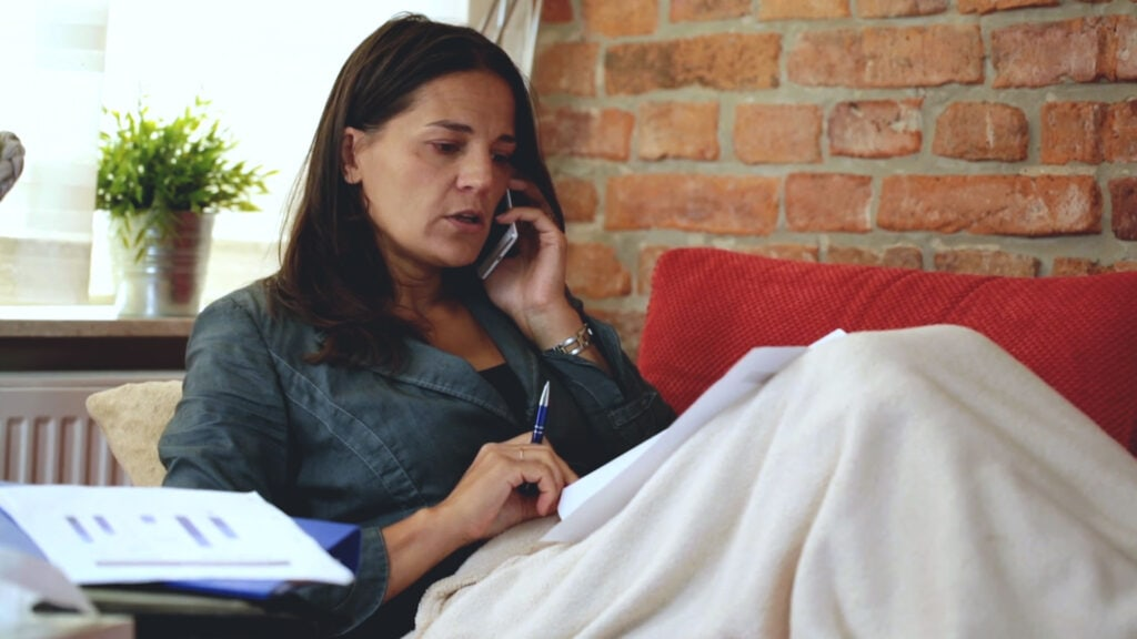 Woman sneezing while trying to work on the couch. Reduce Allergies with Air Duct Cleaning.