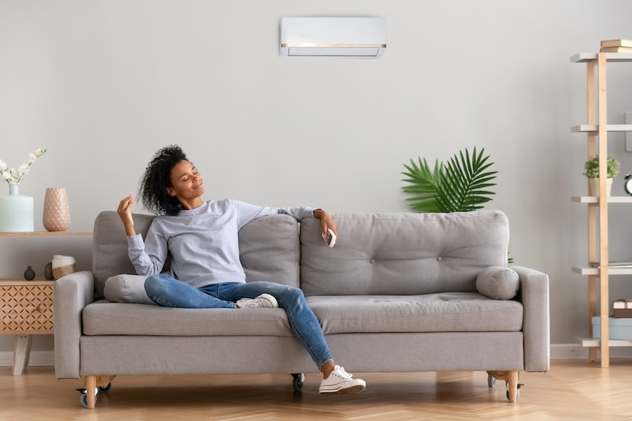 African young relaxed woman sitting on couch breathing fresh air. What Indoor Air Quality Accessories Can Help Keep Me Healthy?